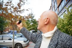An elderly man with a mini camera in his hands, Back view. Stock Photos