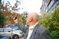 An elderly man with a mini camera in his hands, Back view. Royalty Free Stock Image