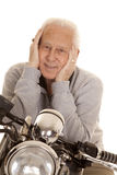 Elderly man on motorcycle close hands face Stock Photos