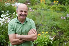 An elderly man with a mustache and a bald spot in a green T-shirt is standing among flowers in the summer garden, arms. Crossed and smiling. Relax in the summer royalty free stock image