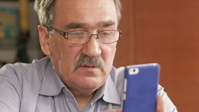 An elderly man with a mustache in glasses dials a text message on his mobile phone. Sits at home at the table. stock video