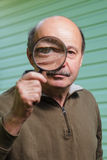 Elderly man with a mustache holding a magnifying glass. Stock Image