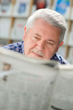 Elderly man with mustache reading paper in library. Senior man with mustache reading newspaper in library Royalty Free Stock Photo