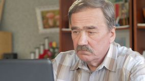 An elderly man with a mustache sits behind a laptop and solves problems. He looks seriously at the monitor stock footage