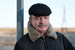 An elderly man with a mustache is wearing a cap Stock Images