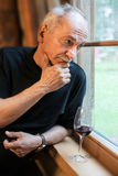 Elderly man near the window with a glass of wine. An elderly man standing near the window with a glass of wine Royalty Free Stock Image