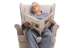 Elderly man with a newspaper sleeping in an armchair stock photos