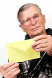 Elderly man opening letter envelope Stock Images