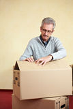 Elderly man opening packing case. Elderly man opening the lid of a packing case while relocation house Stock Image