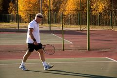 An elderly man over sixty plays tennis. stock photos