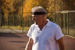An elderly man over sixty plays tennis. royalty free stock image