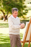Elderly man painting Royalty Free Stock Image