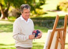 Elderly man painting Stock Images