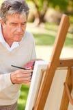 Elderly man painting Stock Image