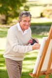 Elderly man painting. In the park stock photography