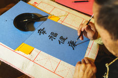 Elderly man painting brush and black ink Japanese characters on blue paper. Stock Image