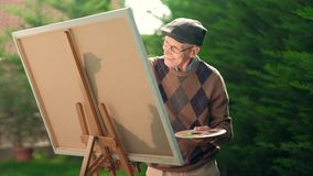 Elderly man painting on a canvas. Outdoors stock video