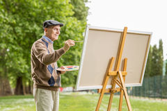 Elderly man painting on a canvas. In the park royalty free stock photos