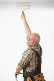 Elderly man painting the ceiling. In white room royalty free stock images