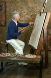 Elderly man painting with easel Stock Image