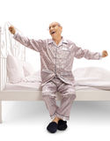 Elderly man in pajamas sitting on a bed and yawning Stock Photography