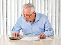 Elderly man with papers. Senior serious man with documents and calculator at home Stock Photography