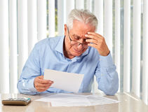 Elderly man with papers. Senior serious man with documents and calculator at home Royalty Free Stock Photo