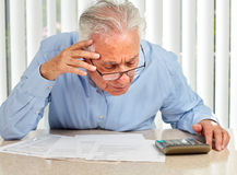 Elderly man with papers. Senior serious man with documents and calculator at home Royalty Free Stock Images