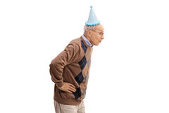 Elderly man with a party hat blowing with his mouth. Isolated on white background royalty free stock photo