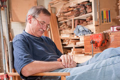 Elderly man peacefully resting in workshop chair Stock Photography