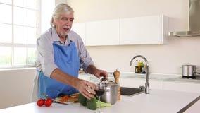 Elderly man peeling carrots and drinking red wine Stock Photo