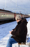 Elderly man with a phone in his hand waiting for train Royalty Free Stock Image