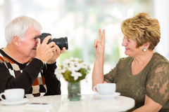 Elderly man photographing wife Royalty Free Stock Photo