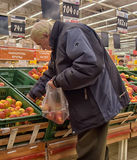 Elderly man picks apples in the supermarket Royalty Free Stock Photography