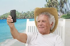 Elderly man picturing himself. Happy senior man on vacation, with cell phone on the beach  picturing himself Stock Images
