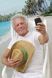 Elderly man picturing himself. Mature man in vacation taking a picture of himself with cell phone at the tropical beach Stock Image