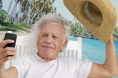 Elderly man picturing himself. Senior man on vacation taking picture of himself on a tropical beach background with  salutation gestural to send to family Royalty Free Stock Photo