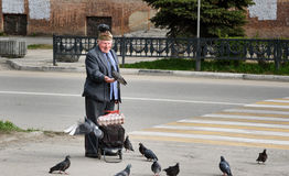 Elderly man with pigeons on the street Royalty Free Stock Photo