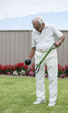 Elderly Man Placing Ball in Artificial Bowling Arm. Stock Photography