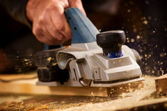 Elderly man planing a plank of wood. Close up of the hand of an elderly man planing a plank of wood in his carpentry workshop with a plane to smooth the surface stock photography