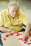 Elderly man playing bingo.