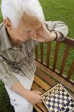 An elderly man playing chess. stock images