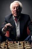 Elderly man playing chess. An elderly man playing chess stock photography
