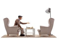 Elderly man playing a game of chess and arguing with an empty ar. Mchair isolated on white background stock photo