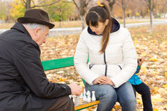 Elderly man playing a game of chess. Elderly men playing a game of chess with a younger women as they sit outdoors on a park bench enjoying the colder weather royalty free stock photos