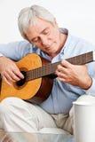 Elderly man playing guitar Royalty Free Stock Image