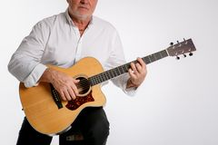 An elderly man is playing a guitar isolated on white background stock image