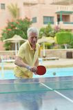 Elderly man playing ping pong Stock Photography