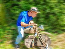 Elderly man playing a wooden motorcycle racer royalty free stock photo