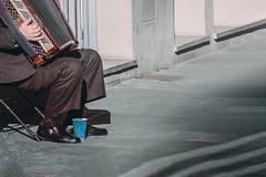 Elderly man plays the accordion on the street stock photos